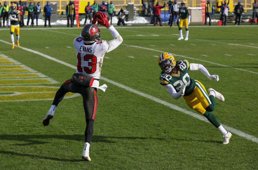 GREEN BAY, WISCONSIN - JANUARY 24: Mike Evans #13 of the Tampa Bay Buccaneers catches a touchdown pass past Kevin King #20 of the Green Bay Packers in the first quarter during the NFC Championship game at Lambeau Field on January 24, 2021 in Green Bay, Wisconsin. (Photo by Dylan Buell/Getty Images)